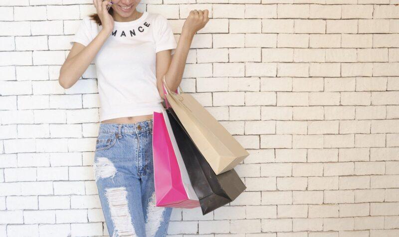ショッピングバッグを手に持ち電話する女性